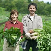 農園で収穫した野菜を持ち微笑む20代の男女