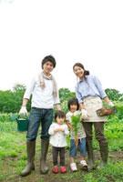 農園で収穫した野菜を持ち微笑む4人家族