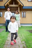 マイホームの前を歩く女の子と両親 20027005540| 写真素材・ストックフォト・画像・イラスト素材|アマナイメージズ