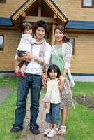 マイホームの前で微笑む4人家族