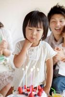 ケーキのろうそくを吹き消す女の子と見守る家族