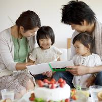 バースデーパーティで娘に絵本を読み聞かせる両親