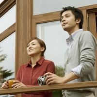 テラスに立ち外を眺める20代のカップル