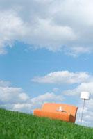青空と草原に置かれた家具のリビングイメージ