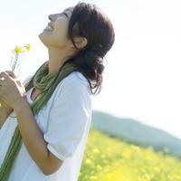 菜の花畑で花を持ち微笑む20代女性