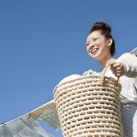 洗濯物を持ち微笑む20代の女性
