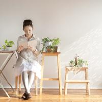 観葉植物に囲まれて本を読む20代の女性