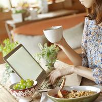 食事をしながらパソコンを見る20代の女性 20027005700| 写真素材・ストックフォト・画像・イラスト素材|アマナイメージズ