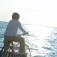 自転車に乗り海辺を見る20代男性の後姿 20027005706| 写真素材・ストックフォト・画像・イラスト素材|アマナイメージズ
