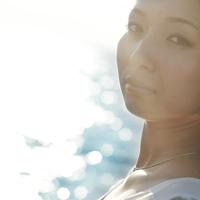 海辺で振り向く20代の女性 20027005715| 写真素材・ストックフォト・画像・イラスト素材|アマナイメージズ