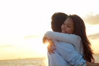 夕日の中で抱き合う20代のカップル
