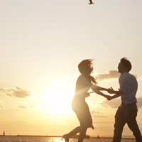 夕日の中で手をつなぎはしゃぐ20代のカップル