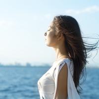 海辺に立ち目を閉じる20代女性の横顔