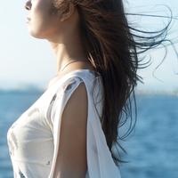 海辺に立ち髪をなびかせる20代の女性