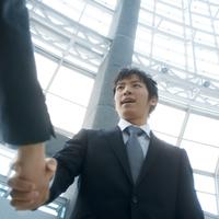 ビルのロビーで握手をするビジネスマン