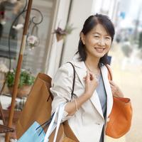 たくさんの買い物袋を持ち微笑むシニア女性
