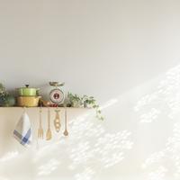 光が差し込む調理器具と野菜を置いたキッチンの棚