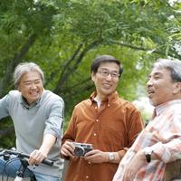 カメラを持ち談笑をする3人のシニア男性