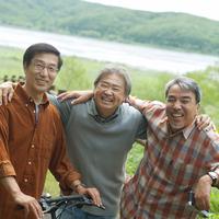 湖の前で肩を組み微笑む3人のシニア男性