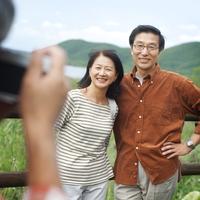 湖の前で記念写真を撮るシニア夫婦