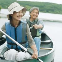 湖でカヌーに乗り微笑むシニア夫婦