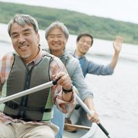 湖でカヌーに乗り微笑む3人のシニア男性