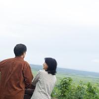 景色を眺め談笑するシニア夫婦の後姿