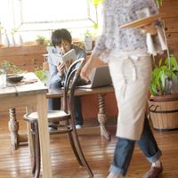 カフェで読書する男性と水を運ぶ女性店員