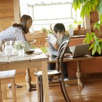 カフェでパソコンをする男性に水を差し出す女性店員