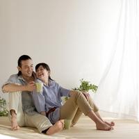 緑のある部屋の床でくつろぐカップル