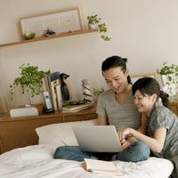 ベッドの上で寄り添いパソコンを見るカップル