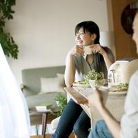 休日に朝食を食べながら窓の外を見る30代のカップル