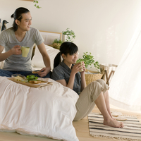ベッドの上で朝食を食べながら窓の外を見るカップル