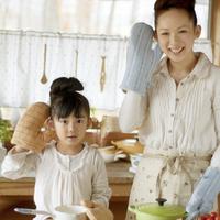 キッチンの料理用ミトンで遊ぶ母親と女の子