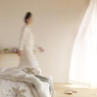 光が差し込む部屋を歩く女性とベッド