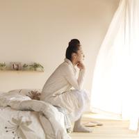 光が差し込む部屋でベッドに座る女性