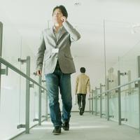 携帯電話で話しながらオフィスの通路を歩く20代男性デザイナー