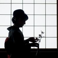 障子の前で花を生けるシニア女性のシルエット
