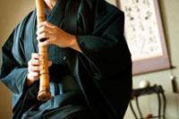 和室で尺八を吹く着物姿のシニア男性の手元