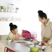 光の差し込むキッチンで料理をする母親と勉強をする女の子