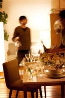 パーティーのセッティングがされたテーブルとグラスを運ぶ男性