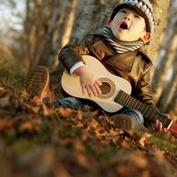 公園でギターを弾きながら歌う男の子