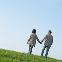 草原で手をつなぎ歩くシニア夫婦の後姿