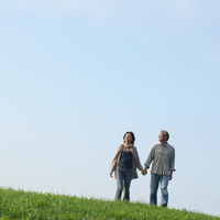 草原で手をつなぎ歩くシニア夫婦