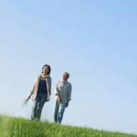 草原で手をつなぎ歩くシニア夫婦 20027006007| 写真素材・ストックフォト・画像・イラスト素材|アマナイメージズ