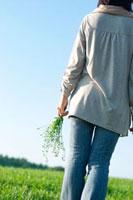 草原で花を持つシニア女性の後姿