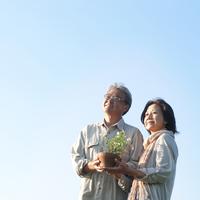 2人で一緒に花の鉢を持つシニア夫婦