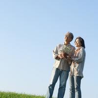 草原で2人で一緒に花の鉢を持つシニア夫婦