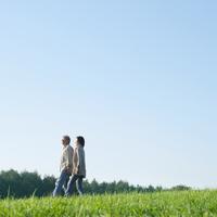 草原を並んで散歩するシニア夫婦 20027006014| 写真素材・ストックフォト・画像・イラスト素材|アマナイメージズ