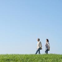 草原を並んで散歩するシニア夫婦